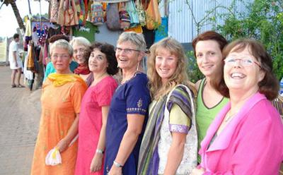 Glada deltagare poserar i indiska saris